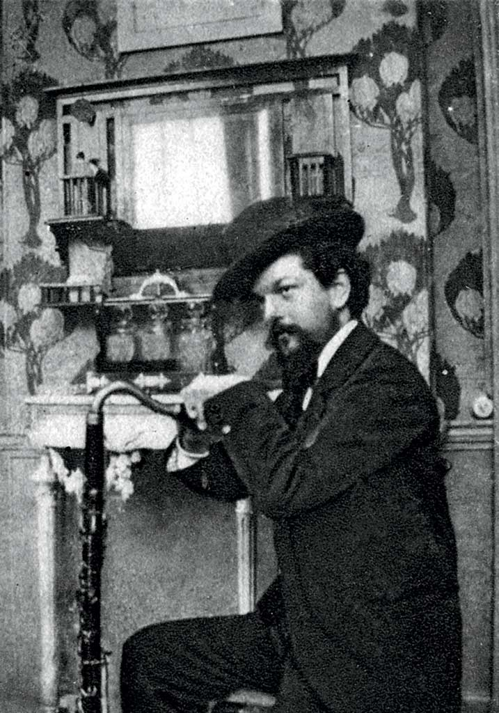 Claude Debussy with hat indoors